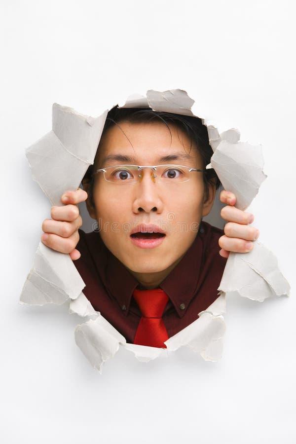 Mann, der überraschend vom Loch in der Wand anstarrt lizenzfreie stockfotografie
