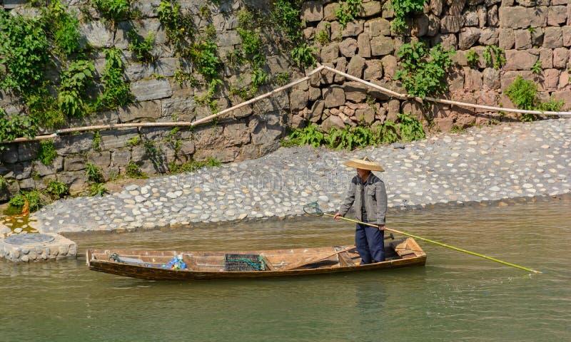 Mann, der Abfall im Fluss sammelt lizenzfreie stockbilder