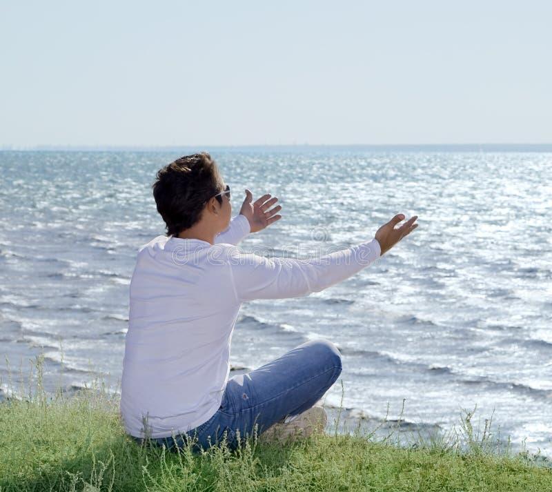 Mann, der am Abgrund sitzt und auf dem Seeufer schaut stockfotos