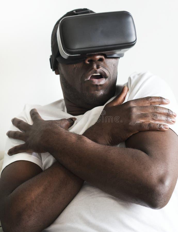 Mann der afrikanischen Abstammung, der VR spielt Spiel verwendet stockfoto