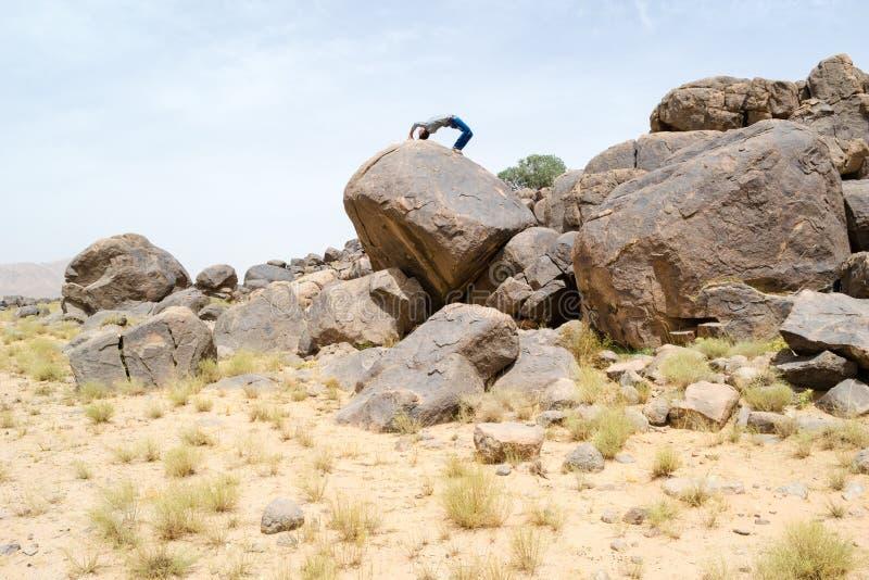 Mann, der akrobatische Bewegungen auf einem Felsen tut lizenzfreie stockfotos