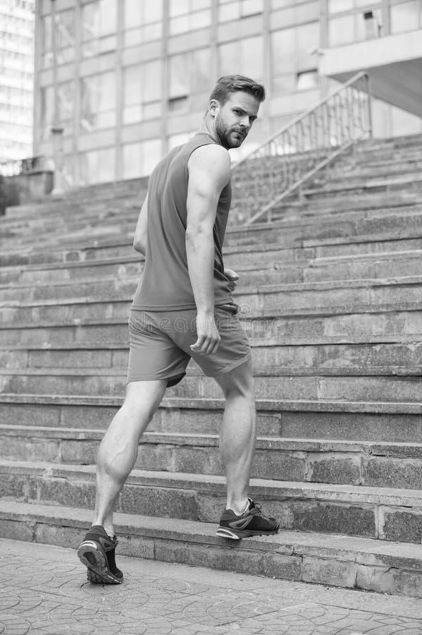 Mann in der aktiven Abnutzung und in den Turnschuhen auf Schritten Sportlertraining auf Treppe Sitz und überzeugtes Zukunft und E stockfotografie