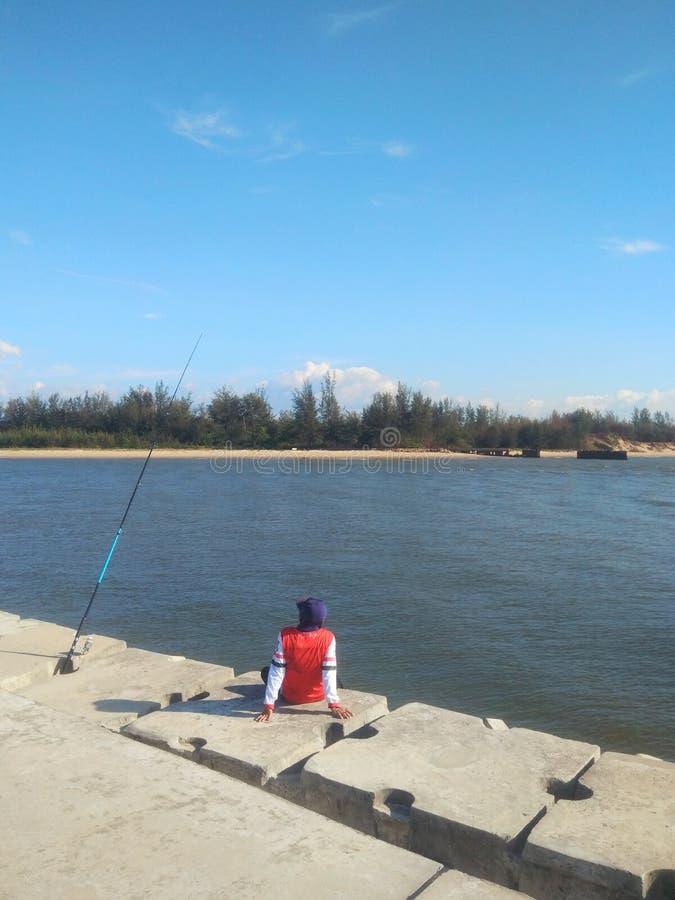 Mann, der allein auf Pierfischent?tigkeit an einem sonnigen Tag - Bild sitzt stockfotos