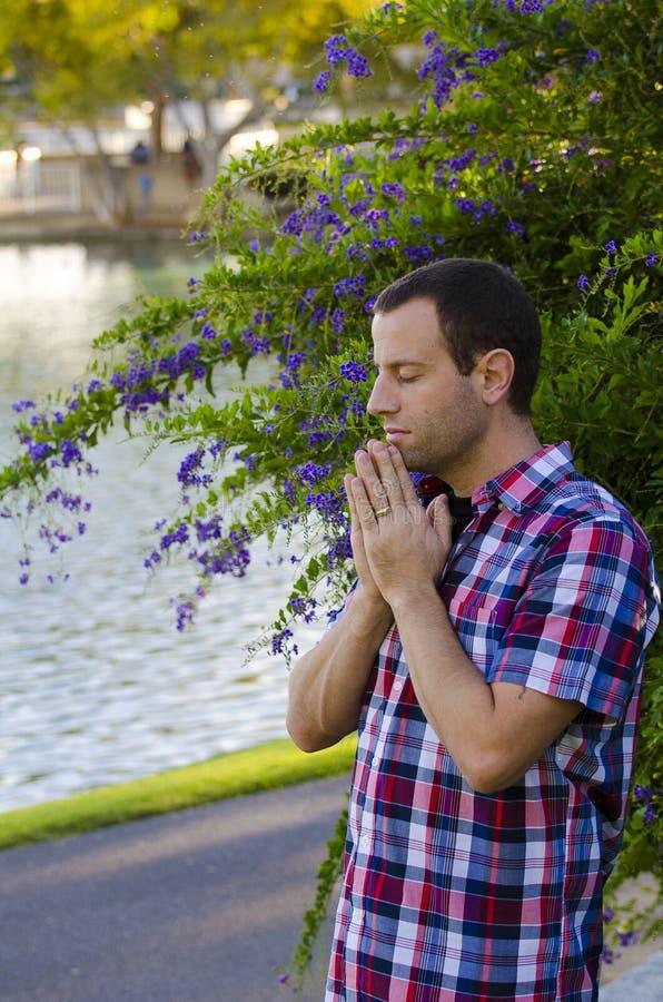 Mann, der allein durch einen See betet lizenzfreie stockbilder