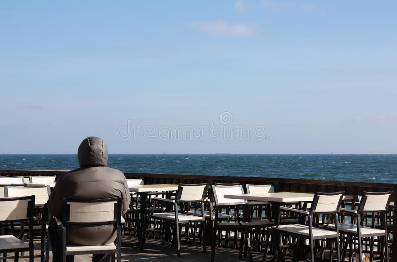 Mann, der allein im Freilichtrestaurant sitzt lizenzfreie stockbilder