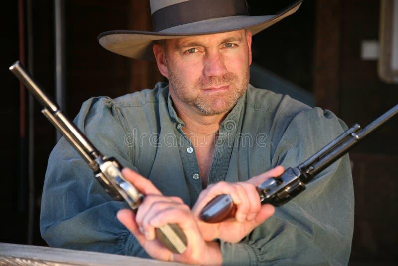 Mann in der alten West-Kleidung zwei Pistolen ausübend lizenzfreies stockbild