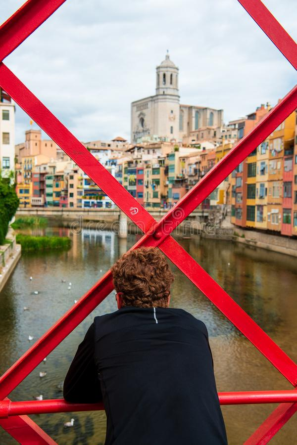 Mann, der Ansicht von Eiffel-Brücke Pont de Les Peixateries Velles über dem Onyar-Fluss in Girona, Spanien betrachtet stockbild