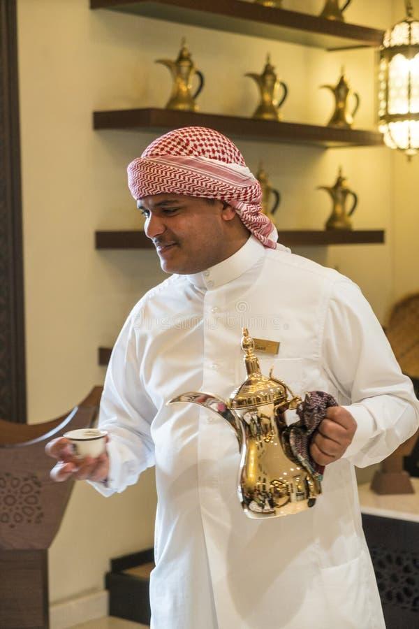 Mann, der arabischen Kaffee von einem traditionellen arabischen Dallah-Kaffeetopf gießt stockbilder