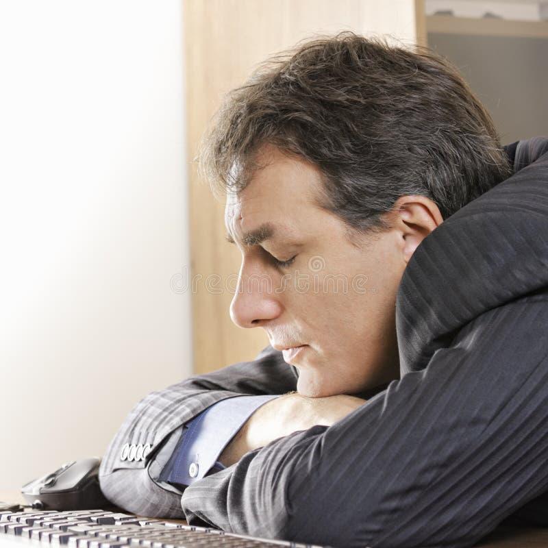 Mann, der auf Arbeitsplatz schläft lizenzfreies stockbild