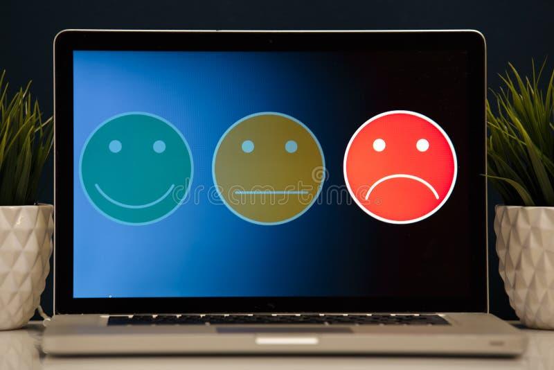 Mann, der auf ausgezeichnete smileygesichtsbewertung für eine Zufriedenheitsumfrage, Kundenerfahrung sich setzt stockfoto