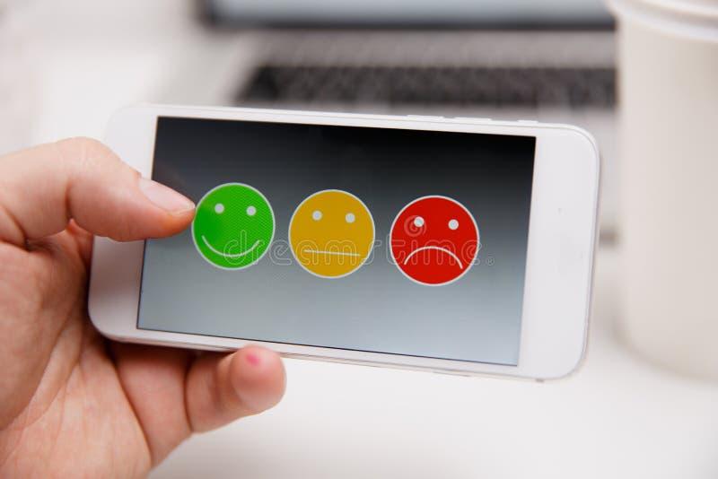 Mann, der auf ausgezeichnete smileygesichtsbewertung für eine Zufriedenheitsumfrage, Kundenerfahrung sich setzt stockbild