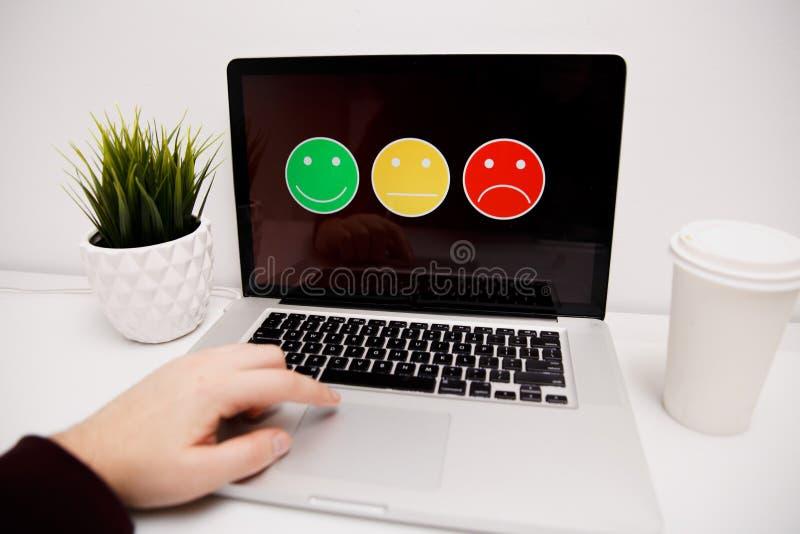 Mann, der auf ausgezeichnete smileygesichtsbewertung für eine Zufriedenheitsumfrage, Kundenerfahrung sich setzt lizenzfreie stockfotos