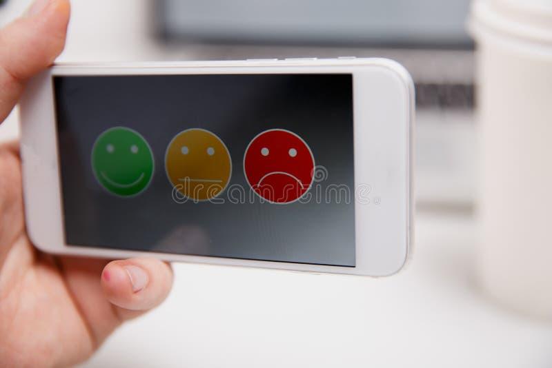 Mann, der auf ausgezeichnete smileygesichtsbewertung für eine Zufriedenheitsumfrage, Kundenerfahrung sich setzt stockfotografie