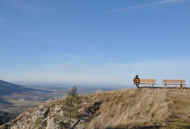 Mann, der auf Bank am Ausblickpunkt sitzt lizenzfreies stockfoto
