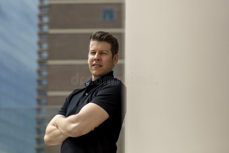 Mann, der auf beige Wand im Freien sich lehnt stockfotos