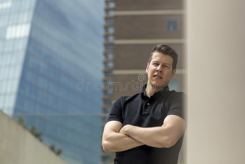 Mann, der auf beige Wand im Freien sich lehnt stockfotografie