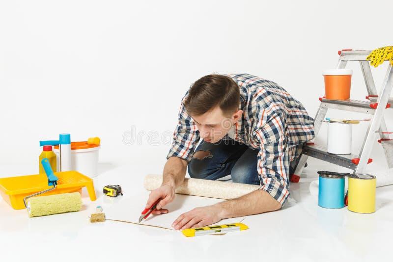 Mann, der auf Boden mit Tapetenrolle, Teppichmesser, Instrumente für den Erneuerungswohnungsraum lokalisiert auf Weiß sitzt lizenzfreie stockfotografie