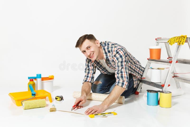 Mann, der auf Boden mit Tapetenrolle, Teppichmesser, Instrumente für den Erneuerungswohnungsraum lokalisiert auf Weiß sitzt stockbild