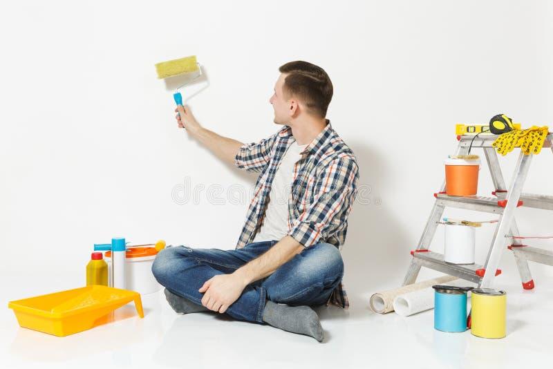 Mann, der auf Boden mit auf Wandfarbenrolle, Instrumente für den Erneuerungswohnungsraum lokalisiert auf weißem Hintergrund sitzt lizenzfreie stockfotos