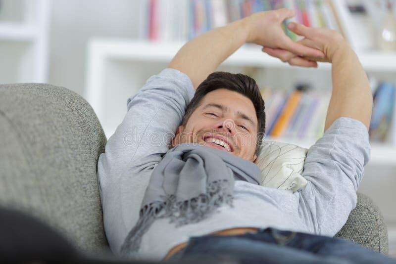 Mann, der auf Couch ausdehnt stockfotografie