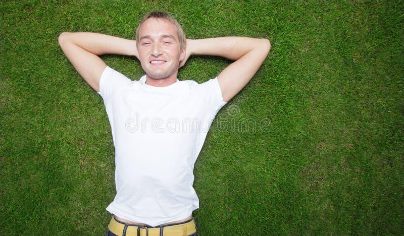 Mann, der auf das Gras legt lizenzfreie stockfotografie