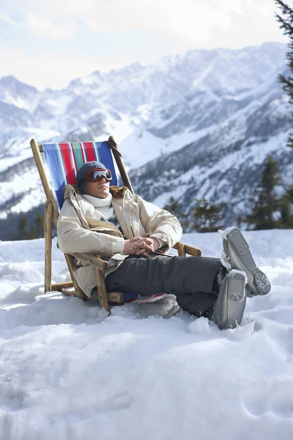 Mann, der auf Deckchair in Snowy-Bergen sitzt stockfotografie