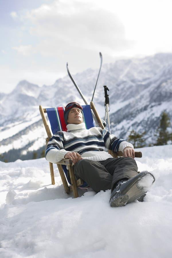 Mann, der auf Deckchair in Snowy-Bergen stillsteht lizenzfreie stockfotografie
