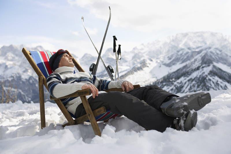 Mann, der auf Deckchair in Snowy-Bergen stillsteht stockfotografie