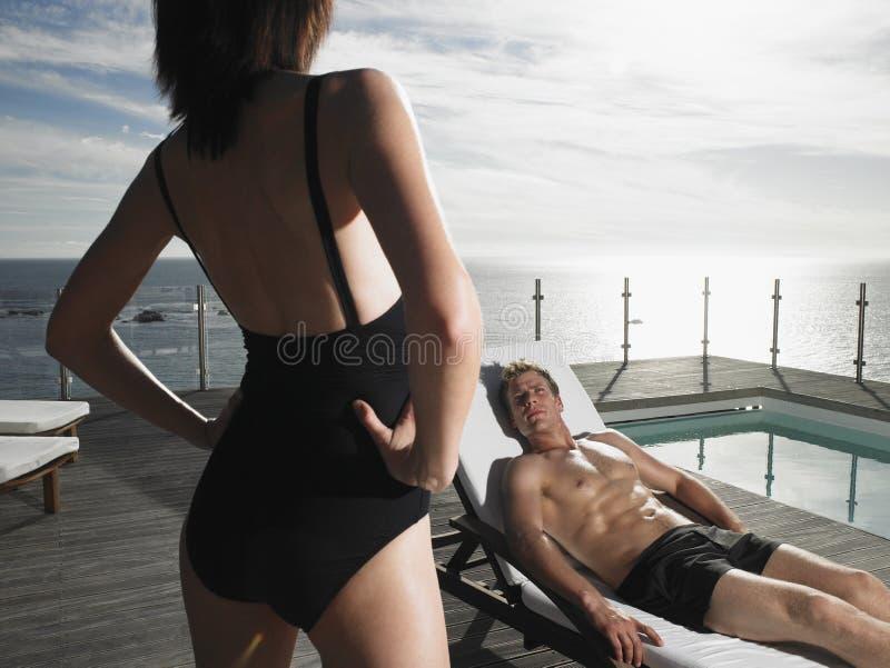 Mann, der auf Deckchair stillsteht und Frau betrachtet lizenzfreie stockfotos