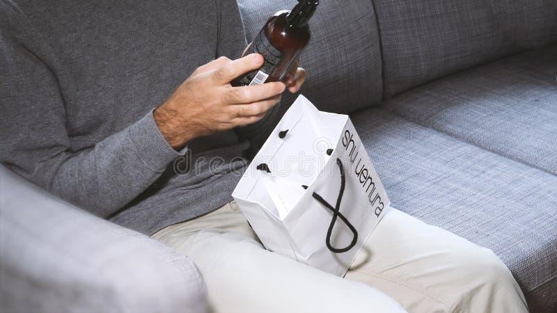 Mann, der auf dem Couchkosmetikenthalten unboxing ist stockbild