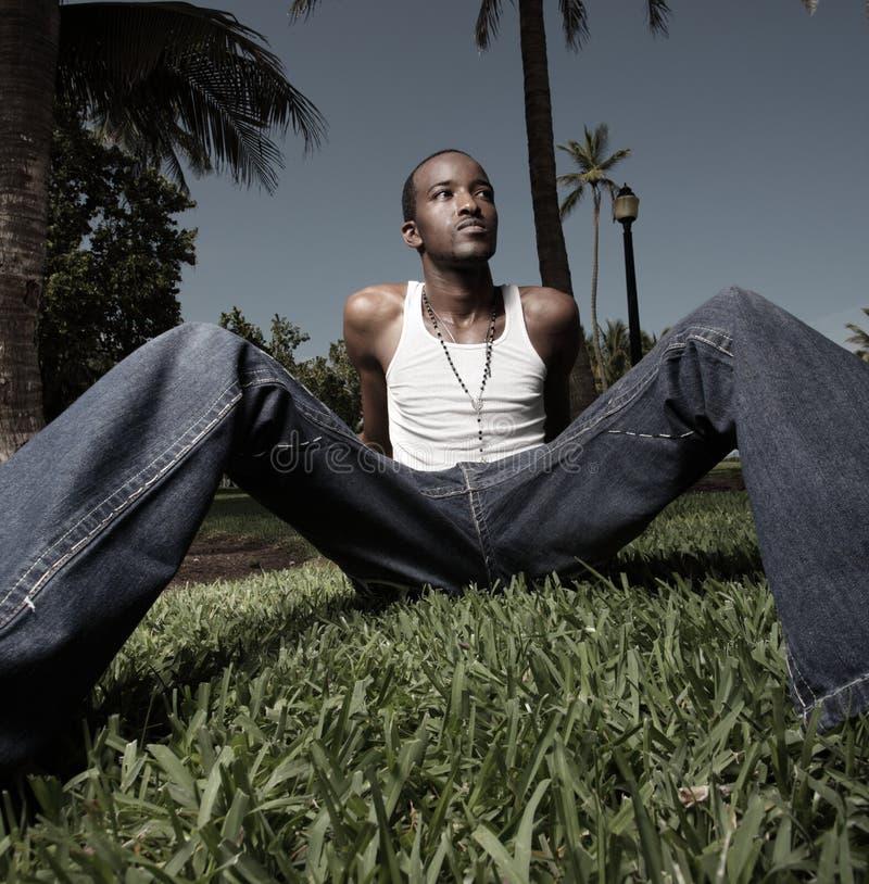 Mann, der auf dem Gras sitzt lizenzfreie stockbilder