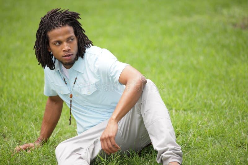 Mann, der auf dem Gras sitzt lizenzfreies stockfoto