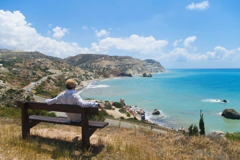 Mann, der auf der Bank betrachtet Meer sitzt stockbild