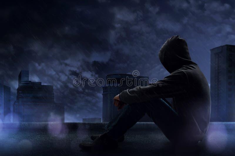 Mann, der auf der Dachspitze sitzt stockfotos