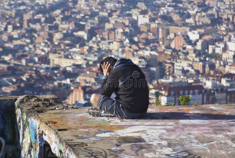 Mann, der auf die Oberseite des verlassenen Gebäudes auf die Oberseite von Barce sitzt lizenzfreie stockfotos