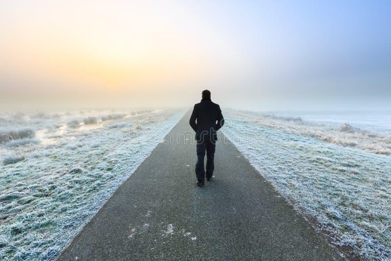 Mann, der auf ein leeres trostloses raod geht lizenzfreies stockfoto