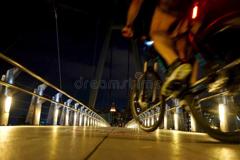 Mann, der auf eine Brücke nachts in Singapur radfährt lizenzfreie stockbilder