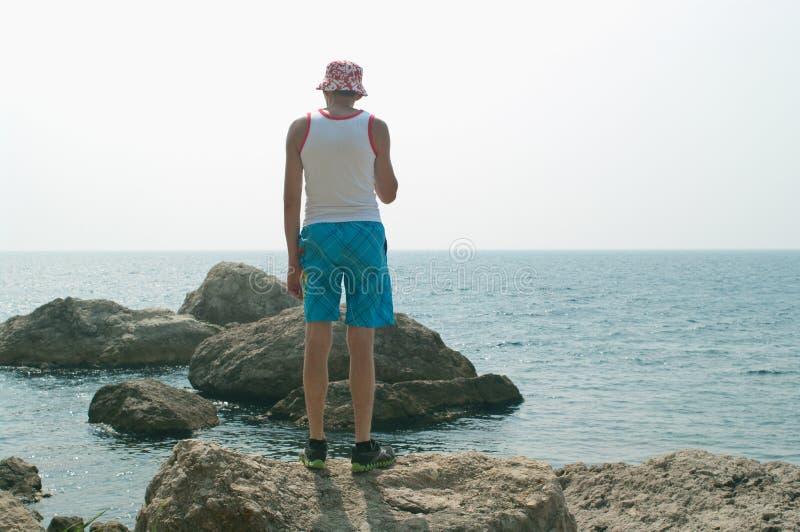 Mann, der auf einem Felsen steht stockbilder