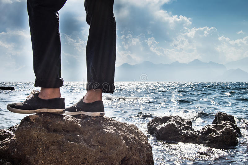 Mann, der auf einem Felsen steht lizenzfreie stockbilder