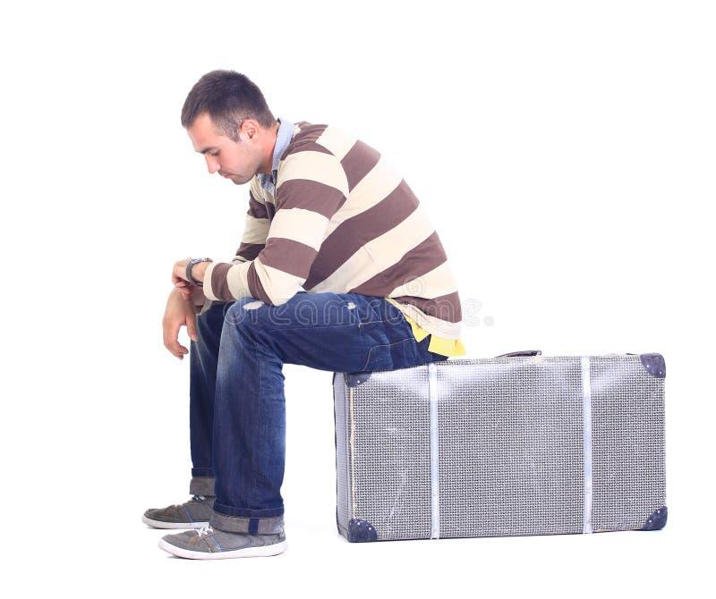 Mann, der auf einem Gepäck sitzt stockfoto