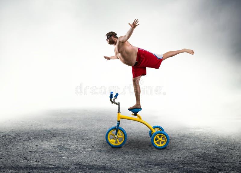 Mann, der auf einem kleinen Fahrrad steht stockfotos