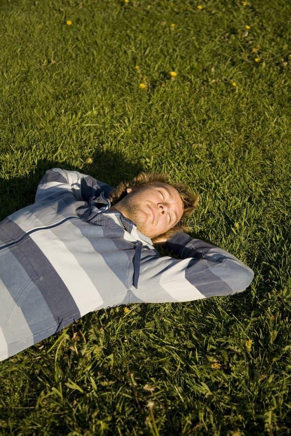 Mann, der auf einem Rasen liegt lizenzfreie stockfotografie