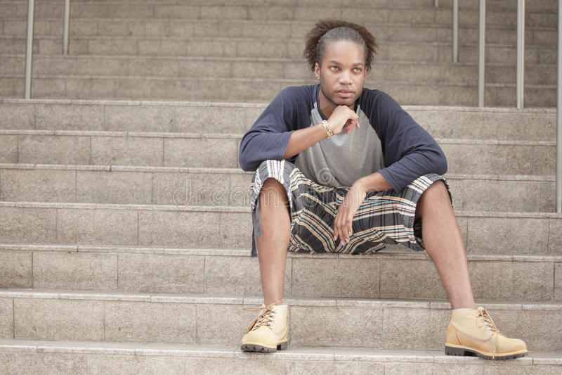 Mann, der auf einem Treppenhaus sitzt lizenzfreie stockfotografie