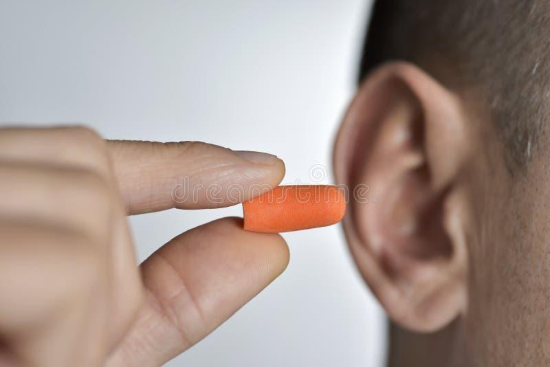 Mann, der auf einen Ohrenpfropfen sich setzt lizenzfreies stockbild