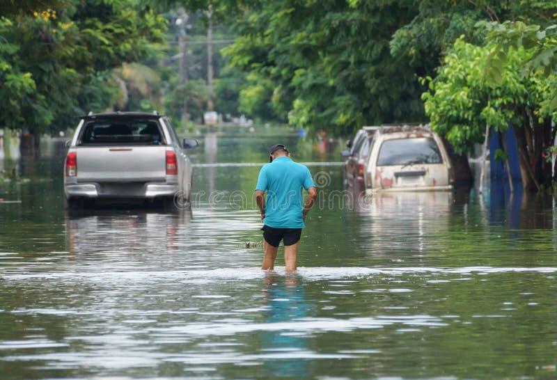 Mann, der auf einer überfluteten Straße spaziert lizenzfreies stockfoto
