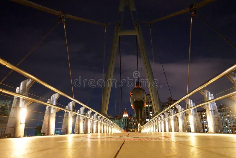 Mann, der auf einer Brücke nachts in Singapur rüttelt stockbild