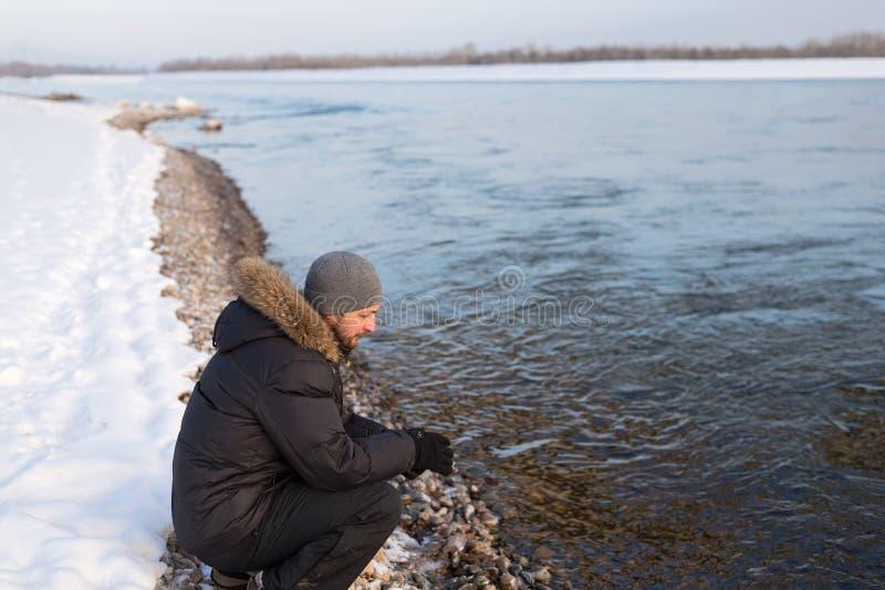 Mann, der auf einer Flussbank sitzt stockfoto
