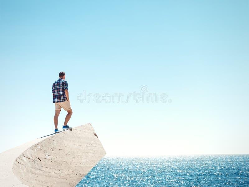 Mann, der auf einer Klippe und einem Meer steht lizenzfreie stockbilder