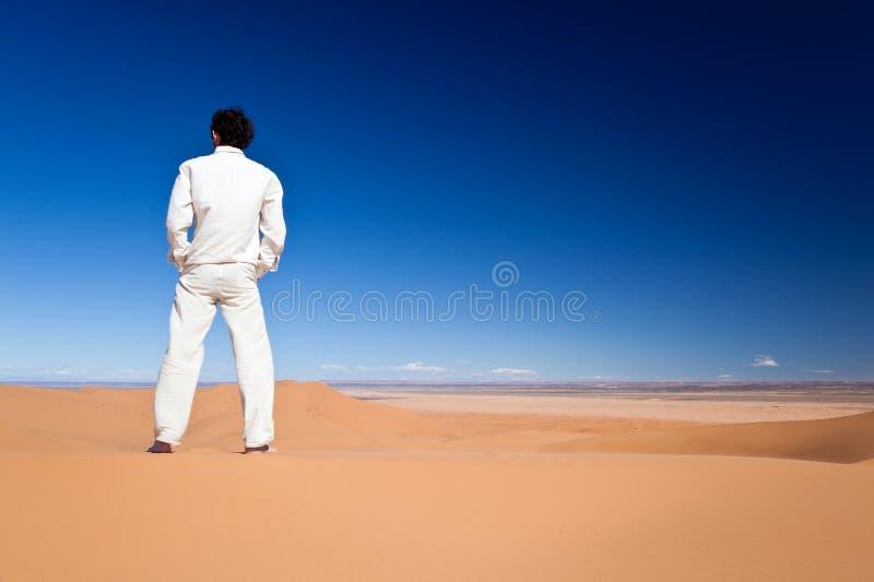 Mann, der auf einer Wüstendüne steht lizenzfreies stockbild