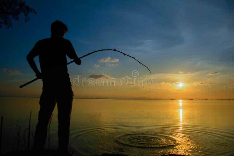 Mann, der auf Fischen bei Sonnenuntergang sitzt lizenzfreies stockbild